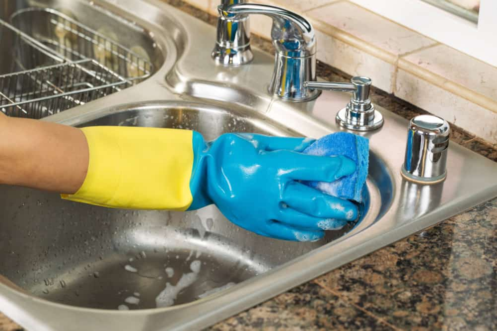 Closeup horizontal image of hand wearing rubber glove washing inside of kitchen sink with sponge and soapy water